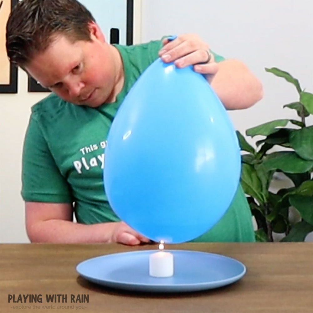 Lower the water filled balloon over the candle
