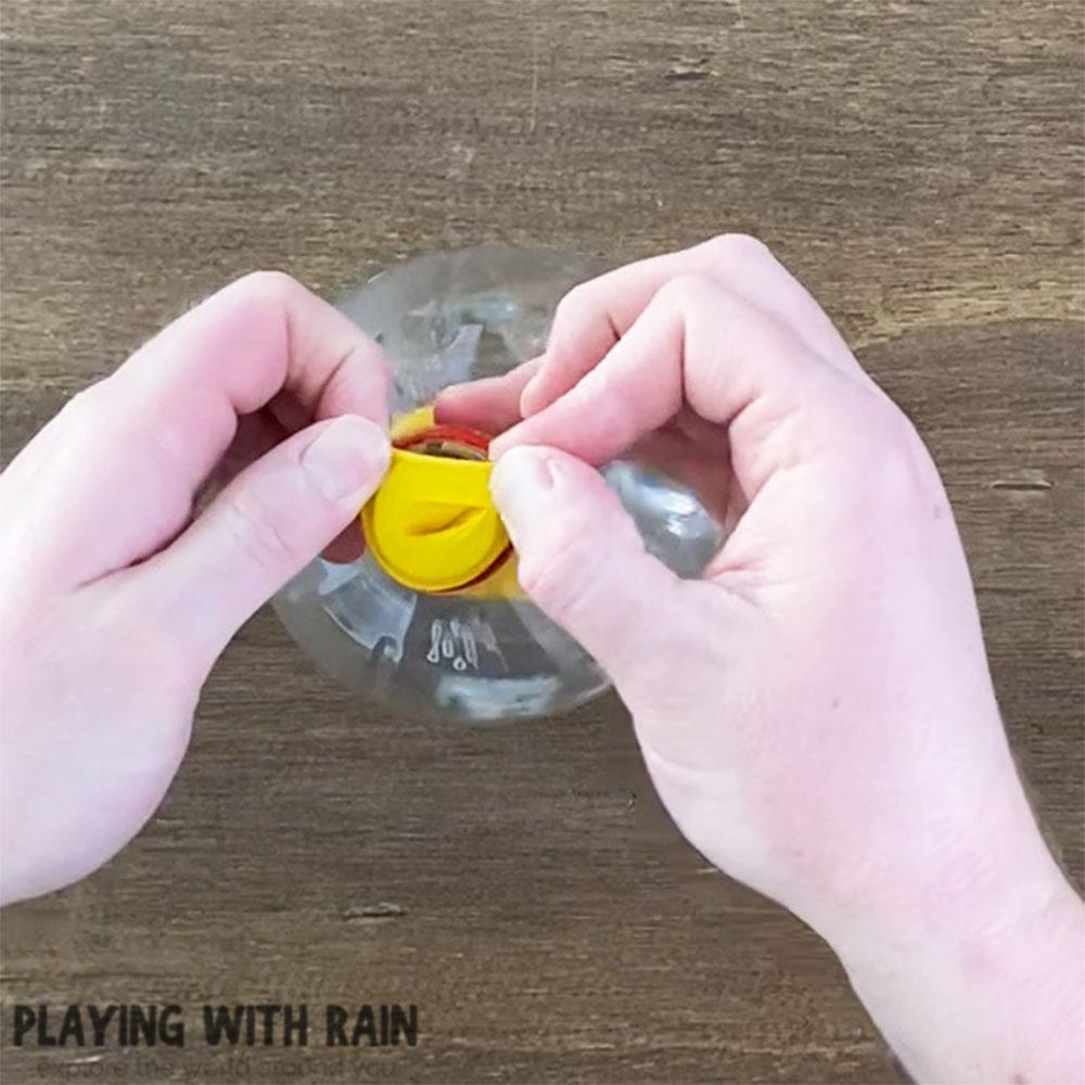 Slide the balloon over the bottle opening