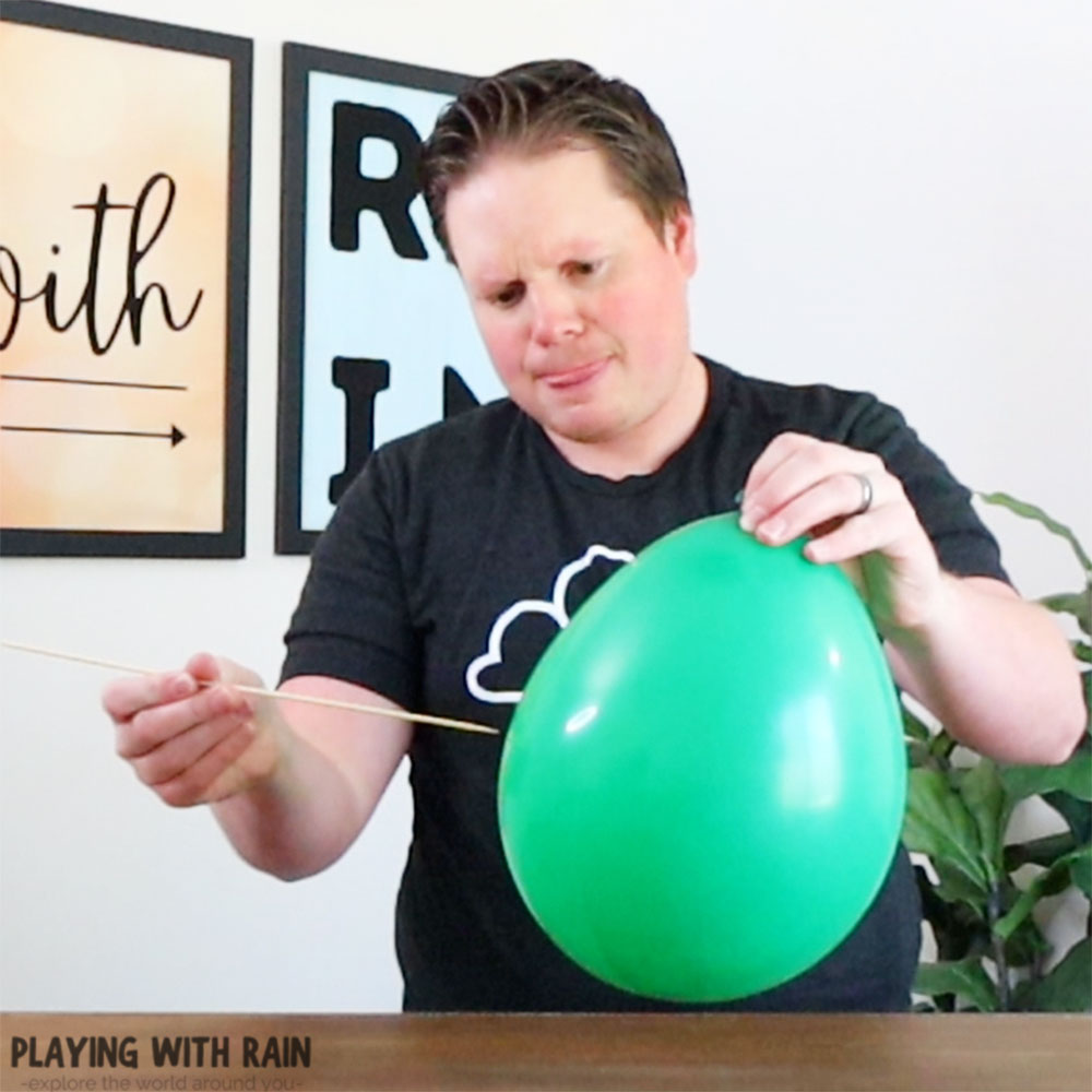 Poke the balloon from the side with a skewer