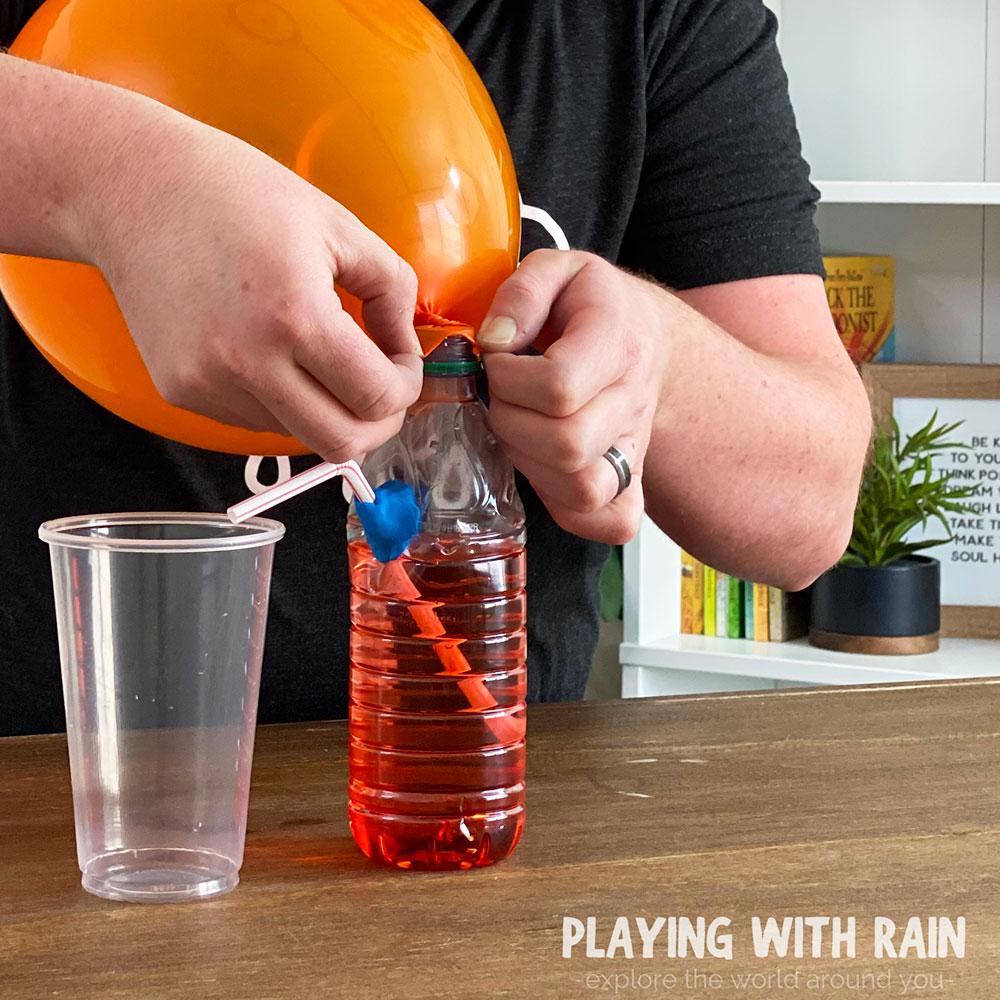 Slide balloon mouth over bottle opening