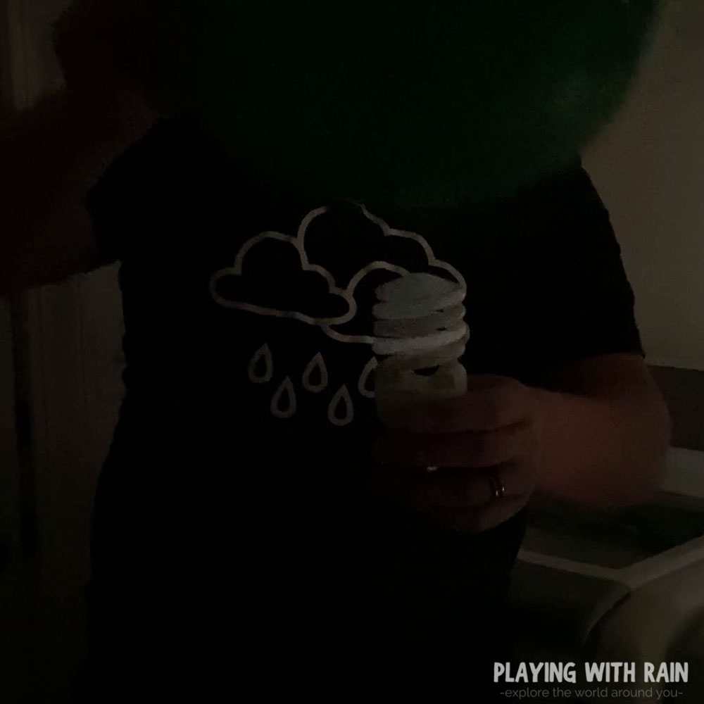 Hold the balloon over the light bulb