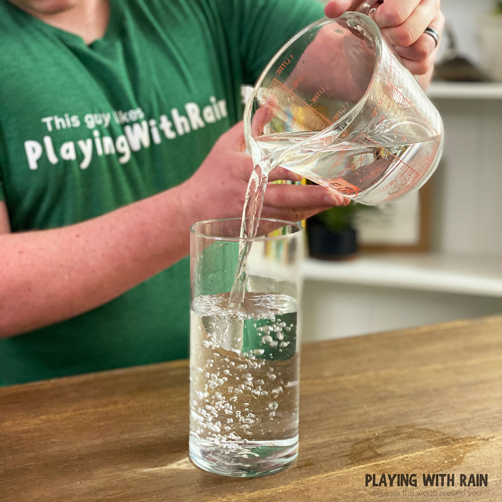 Pour water into a tall, clear glass