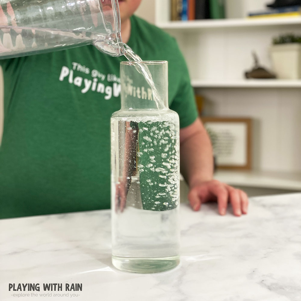 Pouring water into a large pitcher or bowl