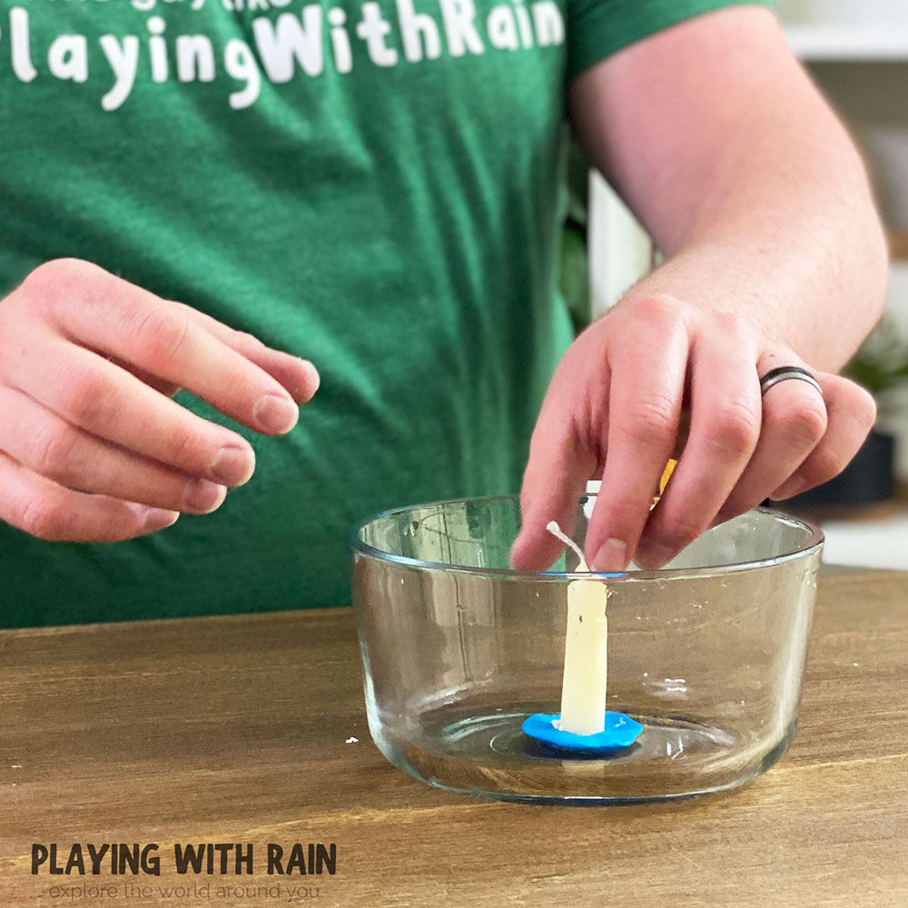 Stand a candle up in a bowl with modeling clay