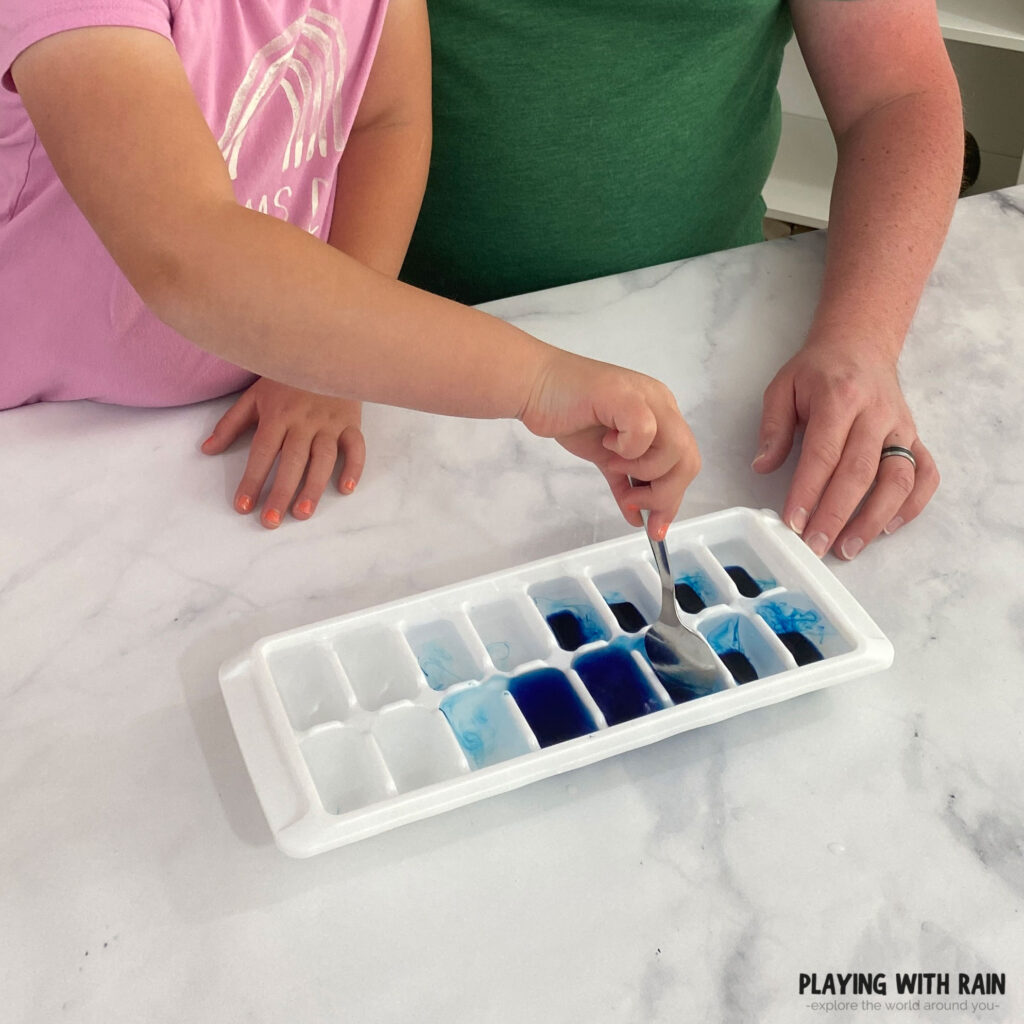 Using a spoon to mix blue food coloring into water