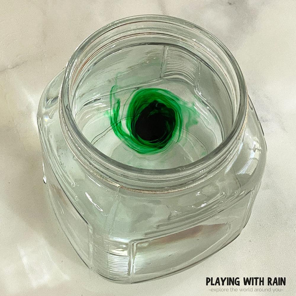 Green food coloring swirling in water